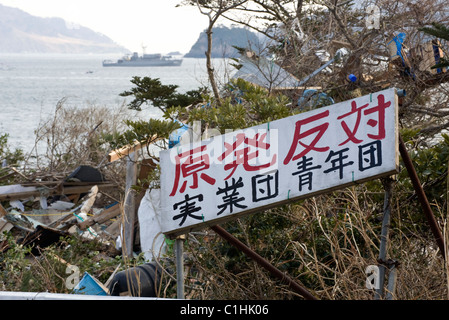 A sign expressing anti-nuclear energy sentiments stands the entrance to the village of Yoriisohama in Ishinomaki - Stock Photo