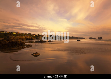 Scenic Bandon Beach Oregon with colorful soft focus sunset reflected in wet sand at low tide and motion blurred - Stock Photo