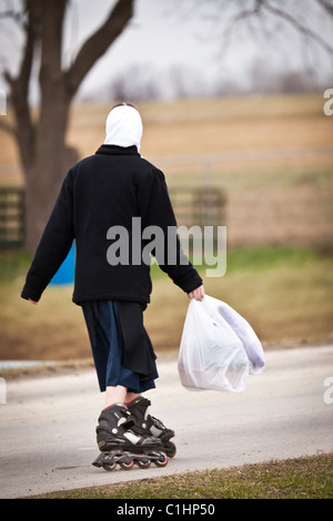 Amish girl roller blades home from school in Gordonville, PA. - Stock Photo