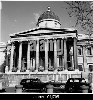 London, 1950s. A photograph by J Allan Cash. Cars and taxis go past the large ornate columned entrance to the National - Stock Photo