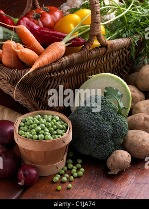 Wicker basket raw vegetables tomatoes sweet red yellow peppers carrots peas cauliflower parsnips broccoli cooking - Stock Photo