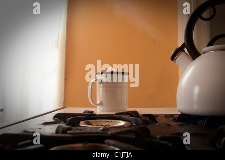 tea pot, cup, and steam on stove - Stock Photo