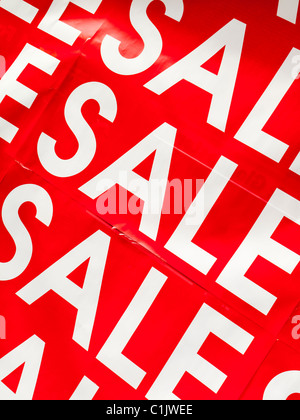Close up view of Sale poster in a shop window with white letters against a bright red background - Stock Photo