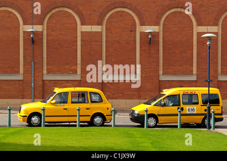 Two licensed yellow taxis parked at a taxi rank in Derby city centre England UK - Stock Photo