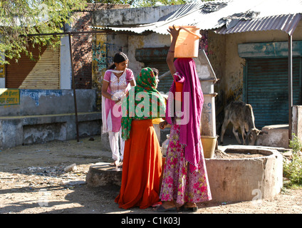 Pretty young village women manually operating a pump to draw fresh clean water from well in rural village of Rajasthan - Stock Photo