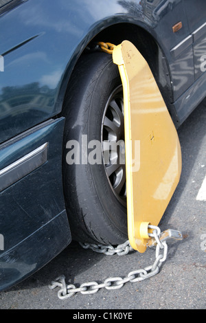 Yellow Police clamp on wheel of untaxed car - Stock Photo