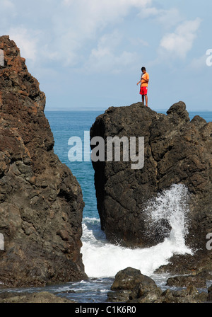 A Costa Rican man fishing from the rocks in Pavones on the Golfo Dulce, Costa Rica - Stock Photo