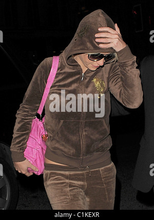 Britney Spears arrives at a hotel wearing a brown velour tracksuit, flanked by her minders. Spears performed in - Stock Photo