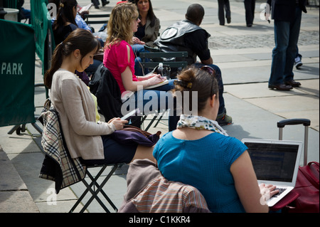 A reader uses her Amazon Kindle electronic book while others use a laptop and music players in Bryant Park in New - Stock Photo