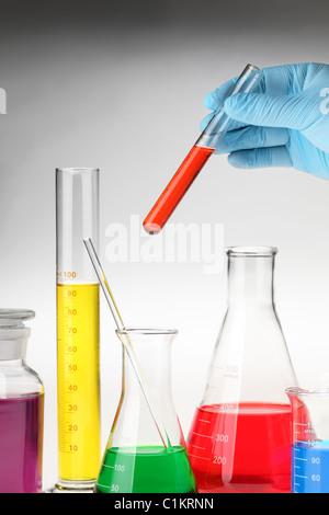 Hand holding test-tube among lab glassware - Stock Photo