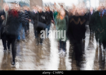 Blurry image of commuters on London Bridge, London, UK, early morning on a winter day - Stock Photo