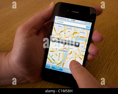 Woman looking at map of London on Google Maps app on Apple iphone 4G smart phone - Stock Photo