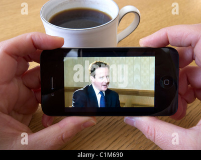 Watching video news of British Prime Minister David Cameron via Youtube on an Apple iphone 4G smart phone - Stock Photo