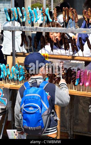 A young school boy enjoys chocolate bananas at a food stall, Ueno Park, Tokyo JP - Stock Photo
