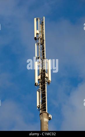 Cellular network antennas on top of a antenna mast - Stock Photo