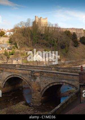 Historic Richmond Castle North Yorkshire with the stone arched Green Bridge over the river Swale in the foreground - Stock Photo
