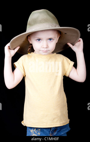 A young girl with a jungle style safari hat on. Her hands are on the hat and she is pulling it down. - Stock Photo