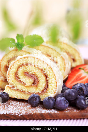 Slices of Swiss roll and fresh blueberries - Stock Photo