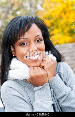 Portrait of happy smiling young black woman outside in the fall