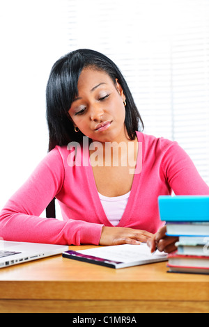 Young black female student studying at desk looking sad - Stock Photo