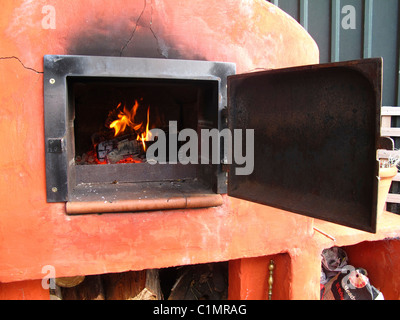 Wood-fired over with old iron stove door fitted - Stock Photo
