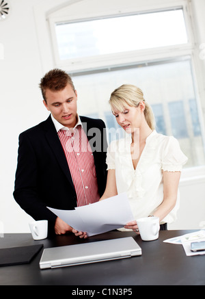 Businessman and woman working in office - Stock Photo