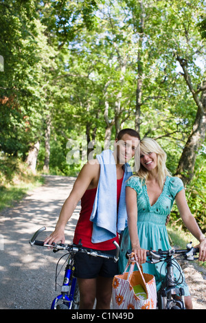 Portrait of young couple with bicycles in forest - Stock Photo