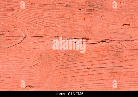 macro of a plank of weathered wood painted red in the sunlight - Stock Photo