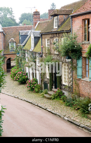 Exterior facade of 18th century French brick house on cobbled street in picturesque village of Gerberoy - Stock Photo
