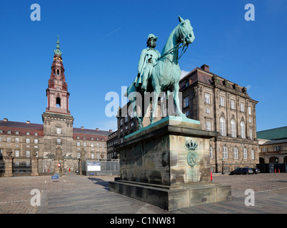 The equestrian statue of King Christian the IX and the main tower of Christiansborg Palace as seen from the riding - Stock Photo