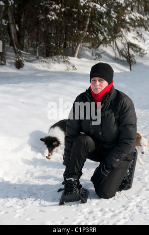 young woman hiking with snowshoes - Stock Photo
