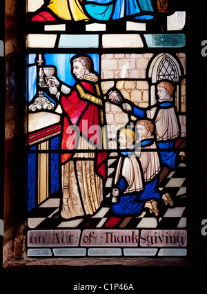 Detail from stained glass window of vicar doing thanksgiving, All Saints Church, Stock village, Essex, UK - Stock Photo