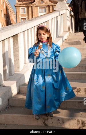 Young girl in costume enjoying an ice cream, the Venice Carnival, Venice Italy - Stock Photo
