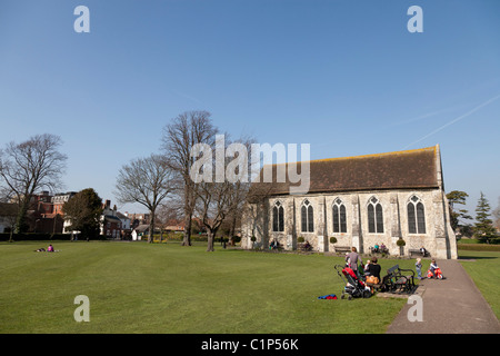 Family enjoying the spring sunshine in Priory park in Chichester city centre and the Guildhall - Stock Photo