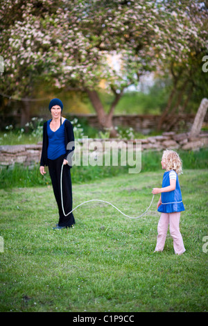 Girl playing with skipping rope in garden with mother - Stock Photo