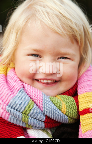 Portrait of small girl wrapped in colorful muffler - Stock Photo