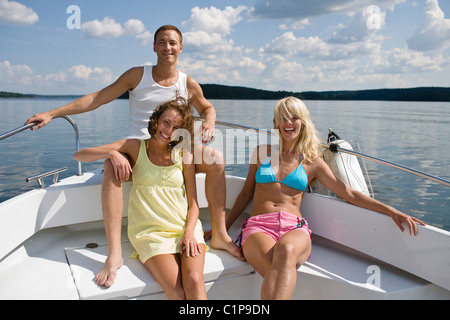 Two young women and young man sitting in yacht on lake - Stock Photo
