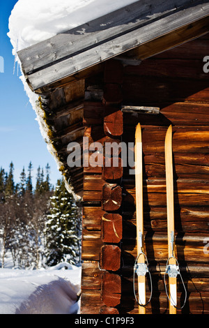 Wooden skies leaning against log cabin in winter - Stock Photo