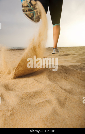 Woman jogging on beach - Stock Photo