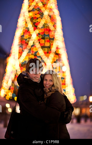 Couple standing in front of illuminated Christmas tree - Stock Photo