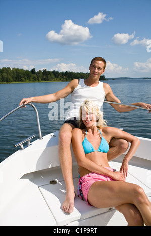 Young couple relaxing in yacht on lake - Stock Photo