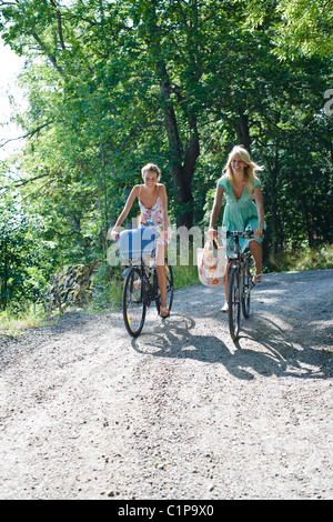 Two young women cycling on dirt track through forest - Stock Photo