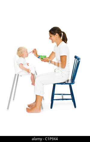 Boy in high chair being fed by mother - Stock Photo
