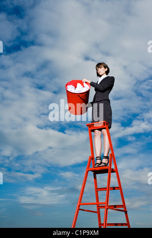 Woman throwing out rubbish from red bin standing on ladder - Stock Photo