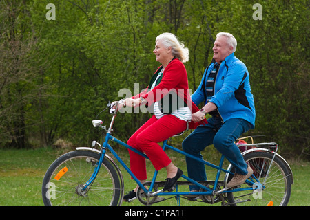 Senior couple riding tandem bike in park - Stock Photo