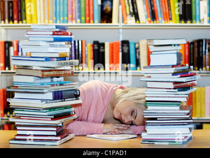 Young woman surrounded by books in library - Stock Photo