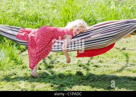 Portrait of girl lying in hammock in field - Stock Photo