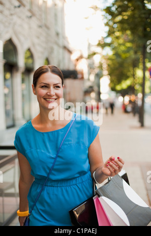 Woman walking through street with carrying shopping bags, smiling - Stock Photo