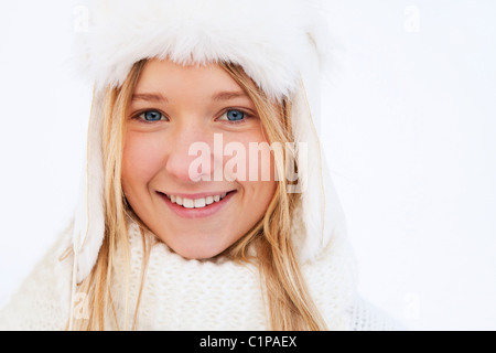 Portrait of teenage girl in white winter clothing - Stock Photo