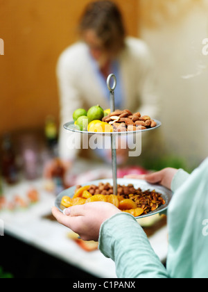 Close up of woman serving fruits and nuts